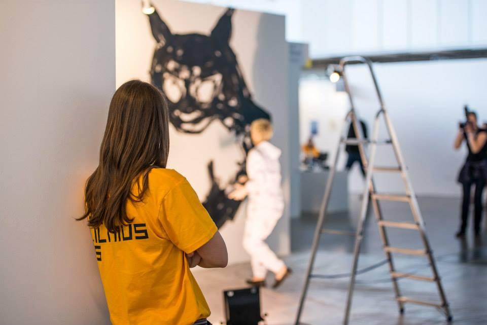 Meno mugės savanoriai mugės ekspozicijų stendus.